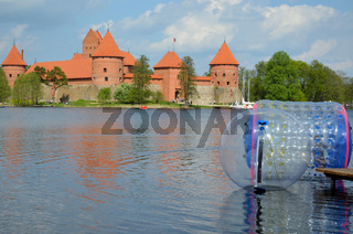Zorbing air bubbles on water. Trakai Castle surrounded by lake Galve. XIV - XV century architecture in Lithuania.