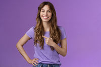 Friendly cheerful charming helpful curly-haired girl give direction suggest promo smiling broadly self-assured confident making good choice grinning assertive stand purple background show copy space