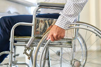 Hand von Senior nach Schlaganfall am Rad vom Rollstuhl