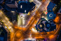 Aerial drone view of night illuminated downtown traffic cirle near the Atrium building, long exposure