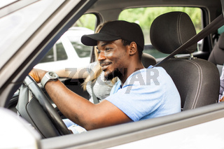 Cheerful young man driving car with friends on vacation