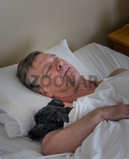 Senior caucasian man and his pet dog asleep in bed illustrating friendship of animals in old age