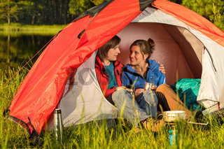 Camping teenagers sitting and embracing in tent