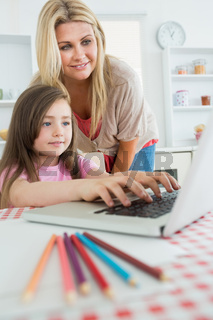 Woman standing looking at Daughter typing