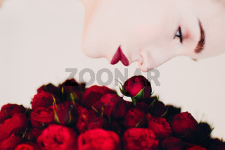 Beautiful woman and red flowers bouguet