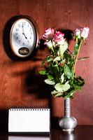 wall clock, blank calendar and pink roses in jug