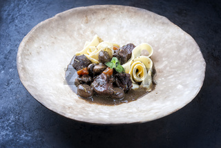 Modern style traditional French boeuf bourguignon with tagliatelle noodles in red wine sauce served as close-up in a rustic design plate
