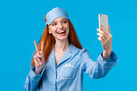 Cute outgoing redhead female want followers check out her new nightwear, extend hand with smartphone, taking selfie and smiling joyfuly make peace gesture express positivity, blue background