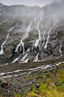 Die vielen Wasserfälle während es regnet in Neuseeland
