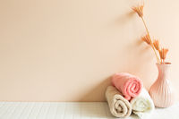 Bathroom towel, vase of plant on white mosaic tile table. pink wall background. Skin care and spa concept. Home interior