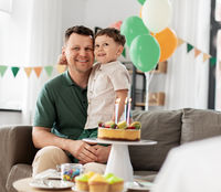 happy father and son with birthday cake at home