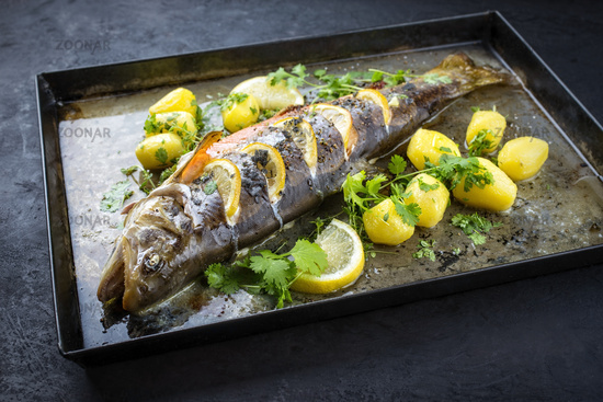 Traditional smoked and roasted char with boiled potatoes and lemon slices offered as close-up on a rustic metal tray