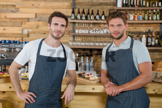 Portrait of smiling waiters standing at counter