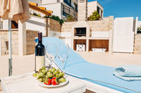 A bottle of wine, two glasses and fruit on the beach near the sunbed. In the shade of an umbrella, in the villa.