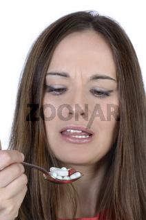 Hübsche Frau mit Löffel voller Tabletten