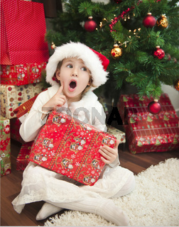 Kind mit Geschenk vor Weihnachtsbaum