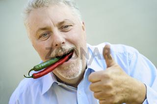 Senior mit roter und grüner Chili