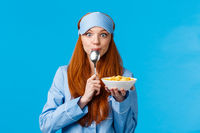 Mmm delicious. Cute pretty foxy teenager college girl licking spoon eating tasty cereals, holding plate, having breakfast wearing sleep mask and nightwear in morning, standing blue background