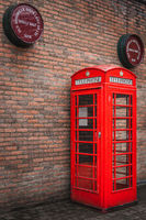 Traditional British public telephone booth with Bushmills whiskey barrels above