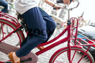 Dutch bicycle driver in Amsterdam/ Netherlands cycling with motion blur. City transportation, tourism and environmental lifestyle concept.