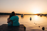 Mom and daughter sitting on a wooden pier, hugging each other