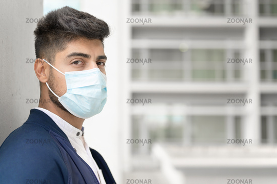 Portrait of a Handsome man in medical mask looking to camera at city. Handsome young man standing outdoors in medical mask. Coronavirus concept.