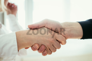 Shaking hands, concept for teamwork: Close up of man and woman shaking hands in the office