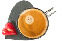 Cup of coffee on stone heart shape soccer, with small red chocolate in shape of heart
