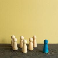 Majority vs minority concept. Wooden human figure on desk. brown background