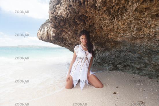 Girl on beach near rock