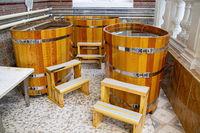 Western style wooden bathtubs in barrel shape. Spa treatments barrels cedar bath in wooden decoration. Wood buckets
