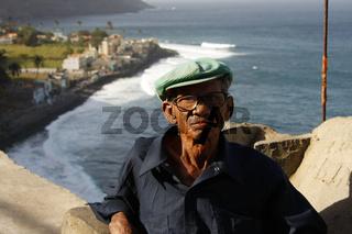aelterer Herr mit Brille in Vila das Pombas an der Kueste der Insel Santo Antao Kapverden |  elderly man with glasses in the small village of Vila das Pombas on the coast of Santo Antao Cape Verde