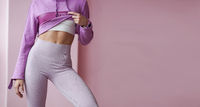 Slender girl in sportswear shows a tight figure and a tummy.