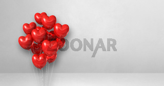 Red heart shape balloons bunch on a white wall background. Horizontal banner.
