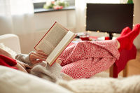 young woman reading book at home on christmas