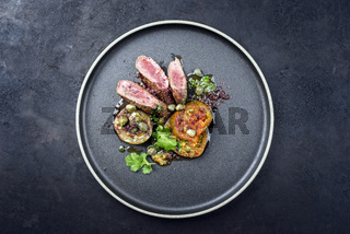 Modern style traditional wild hare back filet braised with tomato slices and capers in herb jus served as top view on a Nordic design plate with copy space