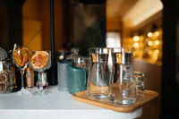 Four glass cups on the bar counter with serving accessories.