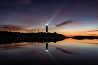 A view of the Cape Trafalgar lighthouse signal light after sunset with colorful evening sky