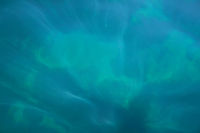 Rays of light falling into the sea.Close up to the waves surface photo.Cool abstract image