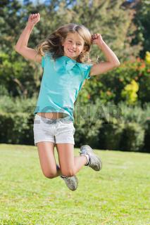 Cute girl jumping and smiling at camera