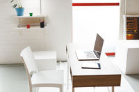 Interior with chair desk laptop and tablet in art studio