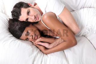 Couple embraced in snug bed