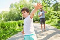 Kind spielt im Park mit Vater beim Handy Telefonat