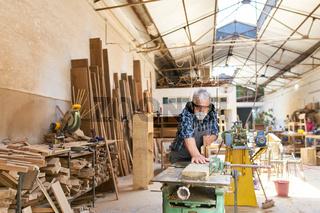 Handwerker in der Schreinerei beim Holz hobeln