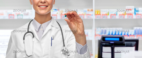 smiling female doctor showing medicine at pharmacy
