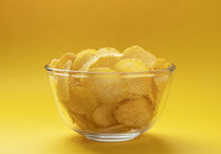 Ridged potato chips in bowl on yellow background