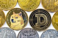 Calgary, Alberta, Canada. May 22, 2021. A couple of Dogecoin with several crypto currency coins around.