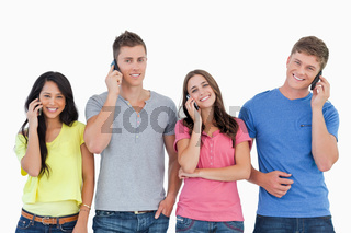 A smiling group of friends make calls while looking into the camera