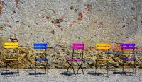colored folding chairs before a brick and stone wall