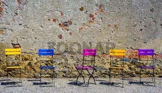 Klappstühle in unterschiedlichen Farben vor einer Stein- und Ziegelwand